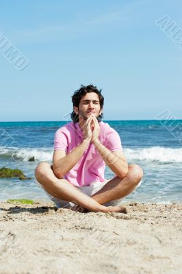 Portrait of young man sitting in lotus pose on sand on beach and
