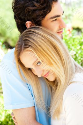 Portrait of love couple embracing outdoor in park looking happy