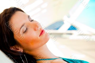 Pretty young woman resting at modern resort. Hotel building at t