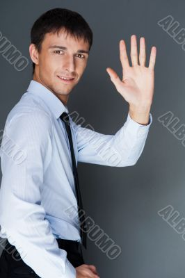 Closeup of a young smiling business man standing confidently aga