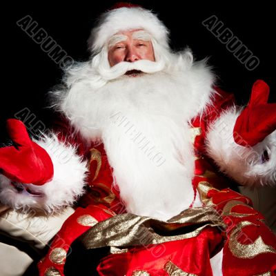 Santa sitting with a sack indoor at dark night room