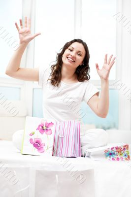 Portrait of young beautiful awake woman with gifts on bed at bed