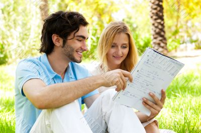 Happy couple of students with a notebook sitting on grass at cam