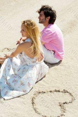 Portrait of young couple sitting together on sand on beach and l