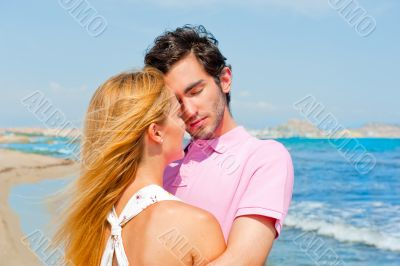 Portrait of young couple in love embracing at beach and enjoying
