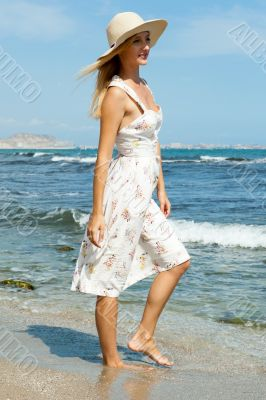 Beautiful elegant young woman at the beach standing, admiring an