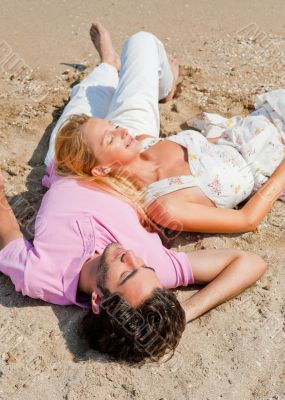 Young couple relaxing on sand at beach and daydreaming with thei