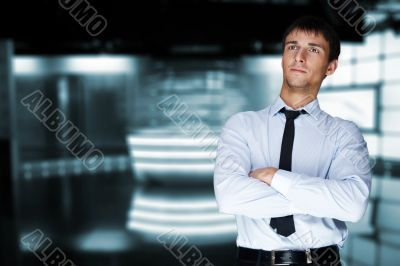 Closeup of a young smiling business man standing in a light and