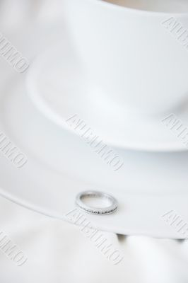 Closeup photo of proposal ring on white plate of coffee cup and