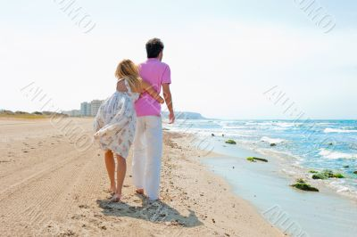 Couple at the beach holding hands and walking. Sunny day, bright