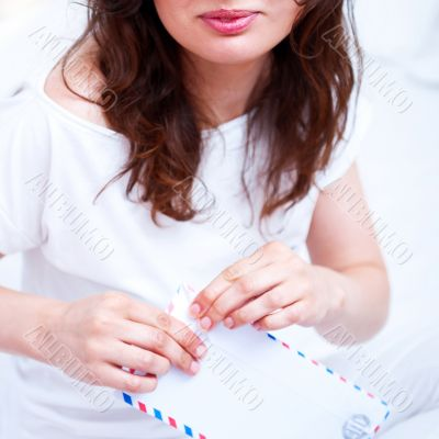 Happy woman reading a letter in her bedroom. She recieved a lett