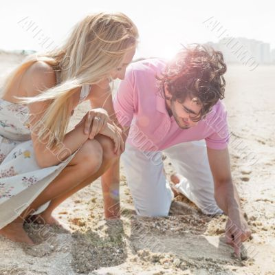 Couple in love drawing a heart in the sand while relaxing at bea