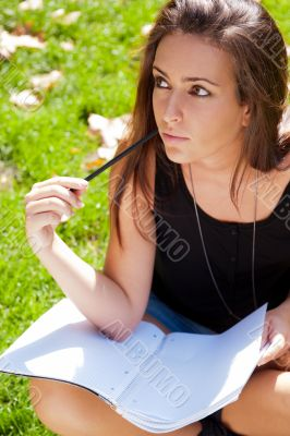 A shot of an caucasian student studying on campus lawn