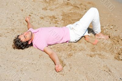 Portrait of attractive and happy man on the beach relaxing and d