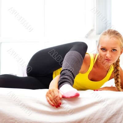 Portrait of beautiful young woman doing exercise at her home