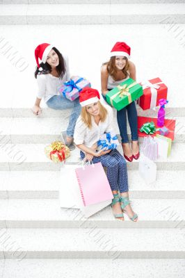 Group of three beautiful girls sitting on stairs at shopping mal