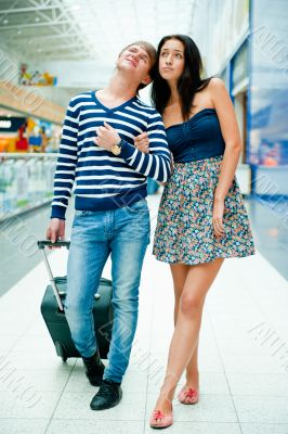 Portrait of young couple walking together at airport hall with t