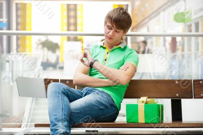 Portrait of young man inside shopping mall with gift box sitting