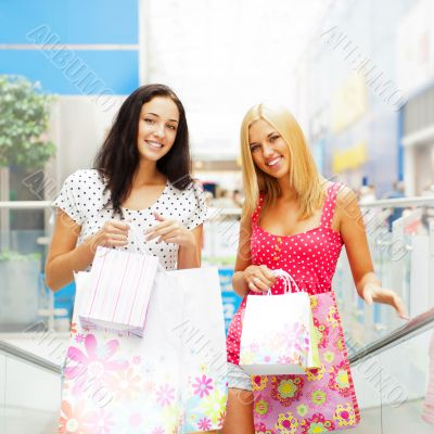 Closeup of two attractive happy girls out shopping. They are mov
