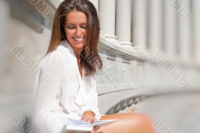 A shot of a smiling college student reading a book at park