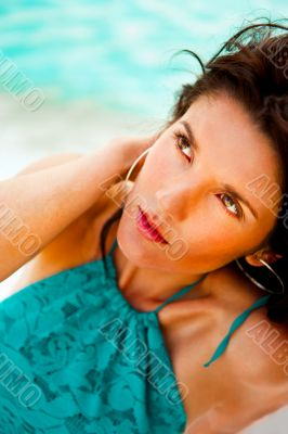 Pretty young woman with hot look and sexy smile sitting on beach