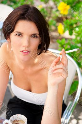 Portrait of a beautiful woman smokes a cigarette outdoor at cafe