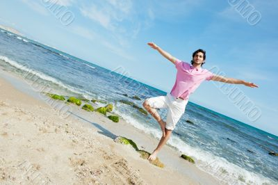Portrait of young man standing carefree with outstretched arms o