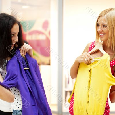 Group of two beautiful shopping women trying on clothes at shopp