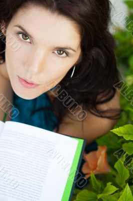 Beautiful girl sitting at park and reads the book. Looking up at