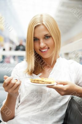 Portrait of young pretty smiling woman eating cake at shopping m