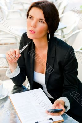 Business woman working with documents while having lunch or brea
