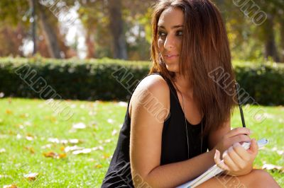 Portrait of a beautiful young female student sitting outdoor at