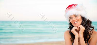 Young beautiful woman wearing christmas hat showing heart shape
