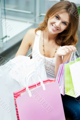Photo of young joyful woman with shopping bags on the background