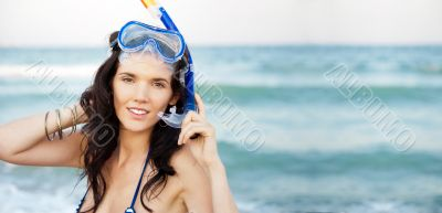 Young hispanic woman with wet skin and with a snorkel standing o