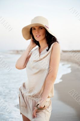 Smiling young woman wearing a straw hat and having fun at the be