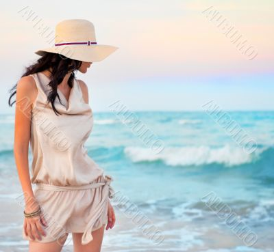 Young beautiful sexy tanned brunette woman wearing straw hat and