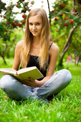 Beautiful female student outdoors with a book at campus park