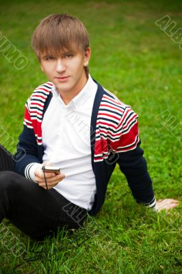 Student outside sitting on grass and holding digital gadget