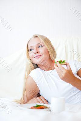 Woman having breakfast in bed. Healthy continental breakfast. Ca