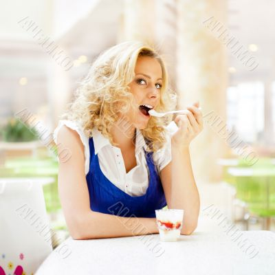 Young woman enjoying coffee time at mall cafe. Eating ice cream