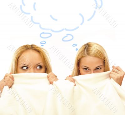 Two women whispering and amazing under blanket