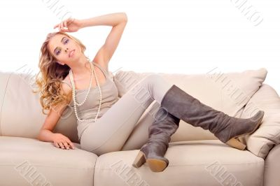 Beautiful woman seated on a sofa in fashionable pose isolated on