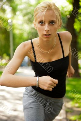 Portrait of young beautiful woman in sportswear running in park.