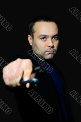 Portrait of a mature man drawing a gun in self defense studio sh