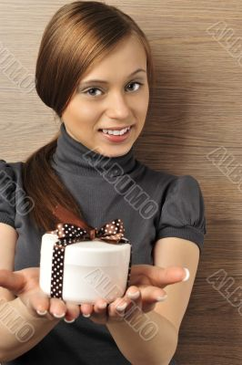 Portrait of a beautiful young woman offering a present.