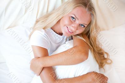 Young blond woman enjoying a sunny morning in bed