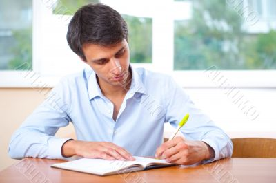 Businessman sitting indoors and writing plan in his diary