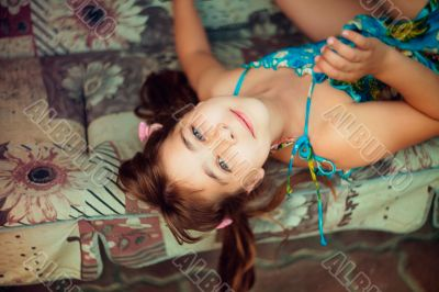 Artistic lifestyle shot of young little girl laying on sofa. Nat