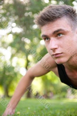 Portrait of young man full of attitude doing pushups on grass at